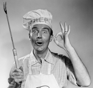 1950s 1960s man wearing chef hat holding barbecue grilling fork making okay sign looking at camera